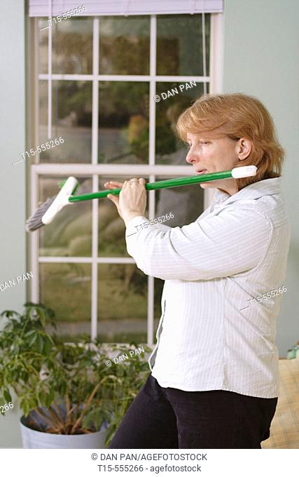 Woman in her 40's doing chore and got bored and using the broom as a flute