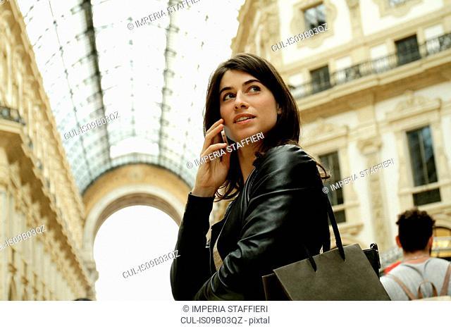 Woman talking on smartphone in Galleria Vittorio Emanuele II, Milan, Italy