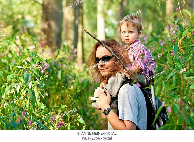 Father with Son on Shoulders in Forest in RIver Sieg wetlands, Germany,lush with tall jewelweed