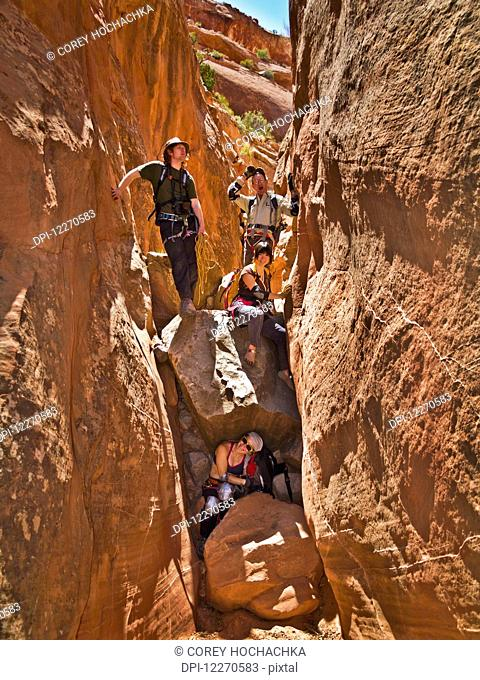 Adventurers exploring a desert slot canyon; Hanksville, Utah, United States of America