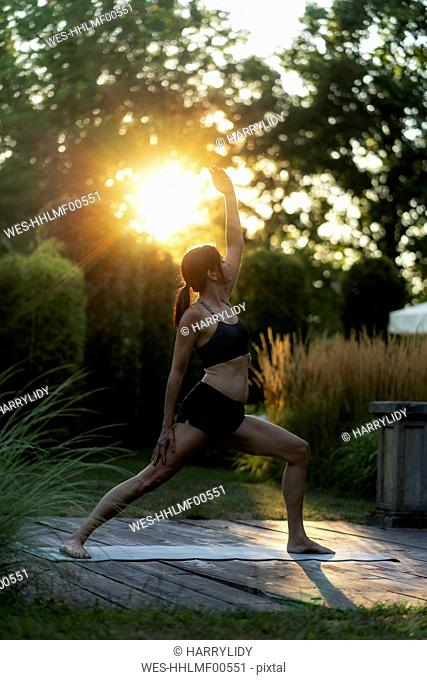 Woman practicing yoga in garden