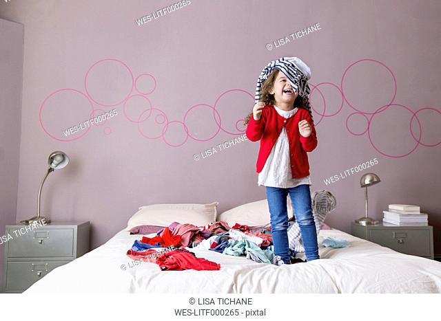 Laughing little girl playing on parents' bed with laundry