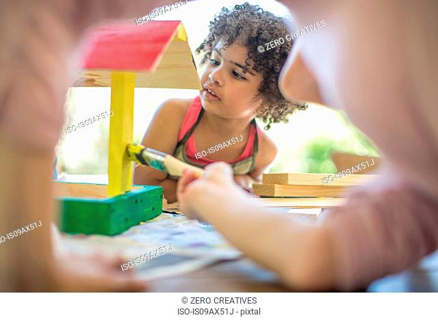 Family doing crafts together, painting wooden birdhouse