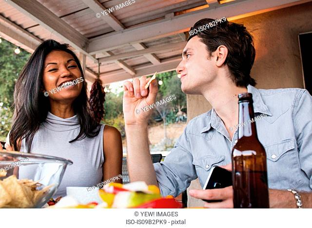 Young couple sitting on veranda, enjoying meal