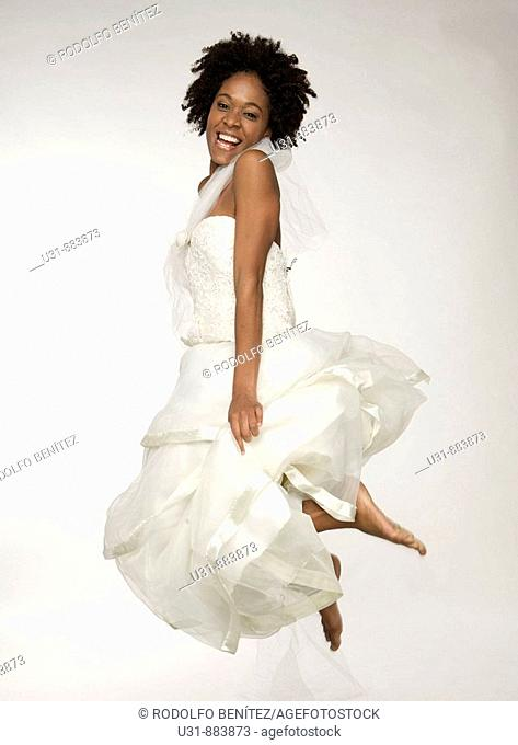 Black Latin girl bride with sexy wavy hair jumps