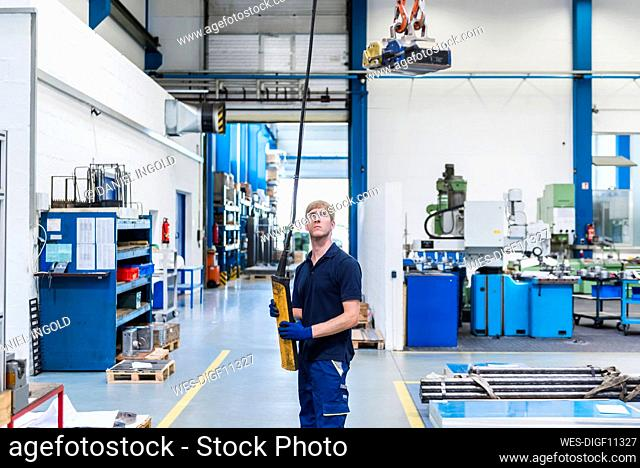 Man working with indoor crane in a factory