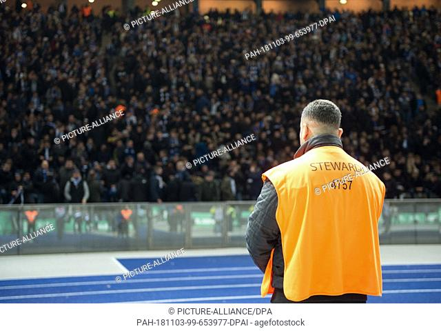03 November 2018, Berlin: Football, Bundesliga, 10th matchday, Hertha BSC Berlin - RB Leipzig in the Olympic Stadium: A safety steward stands in front of the...
