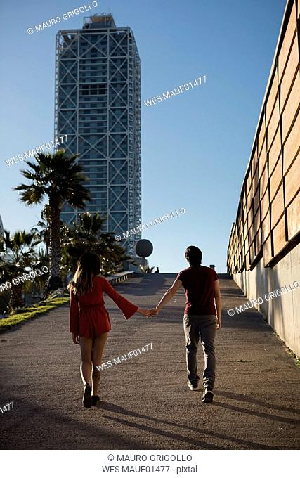 Spain, Barcelona, couple walking hand in hand in the city