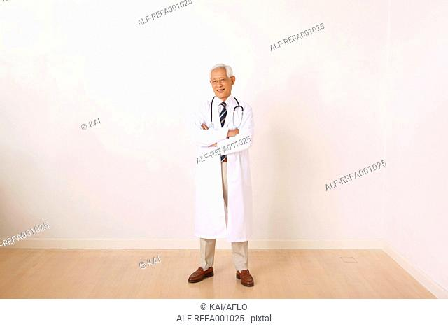 Senior adult Japanese doctor against white wall
