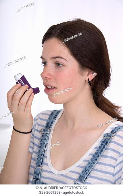 Teenage girl using an inhaler, suffering from Asthma