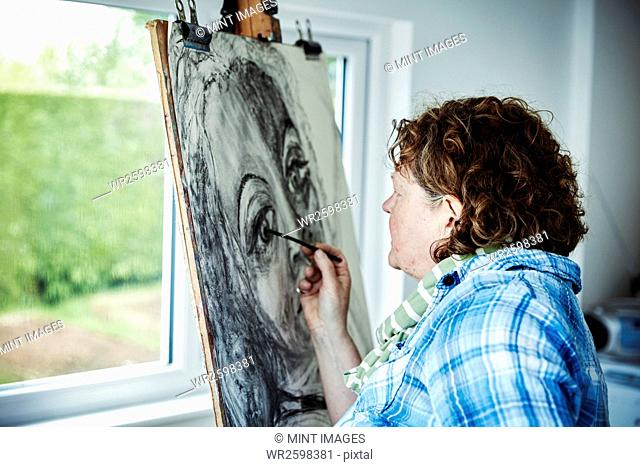 An artist working at her easel, using charcoal on paper drawing a portrait
