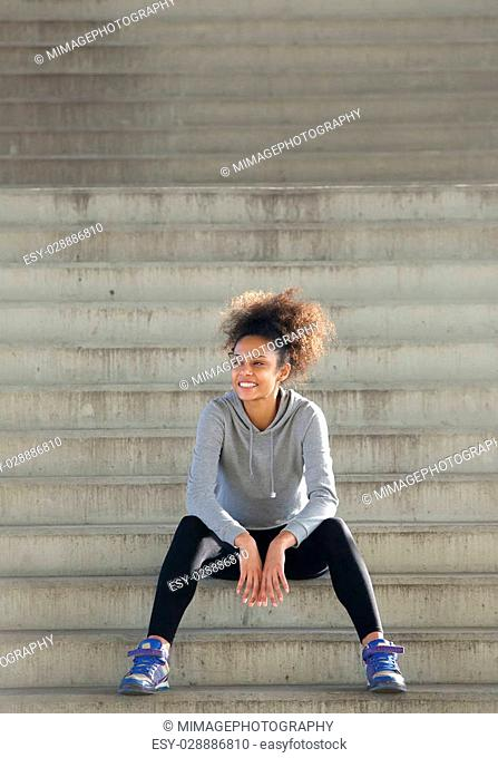 Portrait of a happy young sports woman sitting on steps outdoors