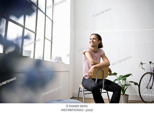 Young woman sitting on chair, looking out of window