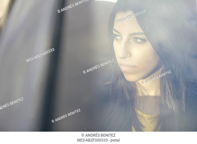 Portrait of young woman sitting in a car looking through window
