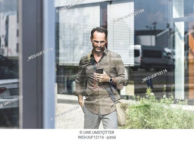 Smiling businessman using smartphone and earphones