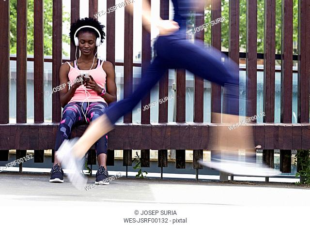 Sporty young women relaxing with runner passing by