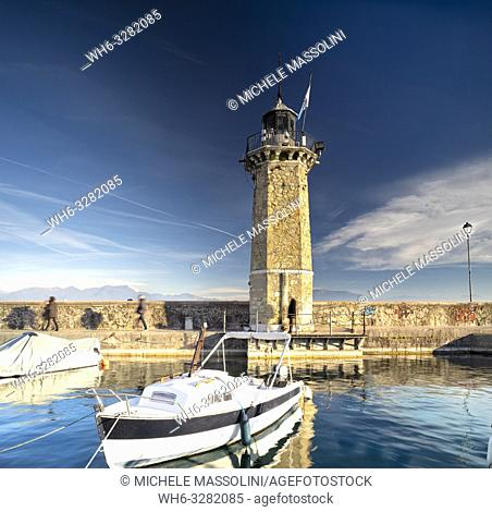 lighthouse tower in the port of Desenzano del Garda with boat