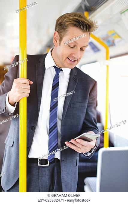 Formal businessman standing on a train. He is holding the handrail with one hand and a smartphone in the other, which he is looking down at