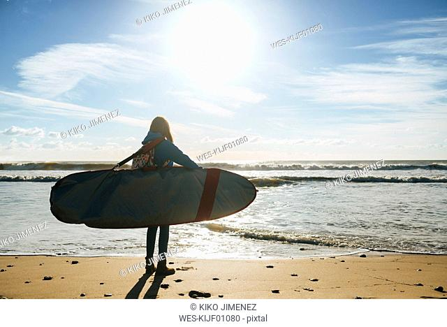 Back view of young woman with surfboard on the beach