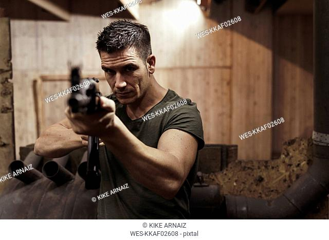 Portrait of man aiming with a rifle in an indoor shooting range