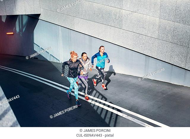 Three female runners racing up city underpass
