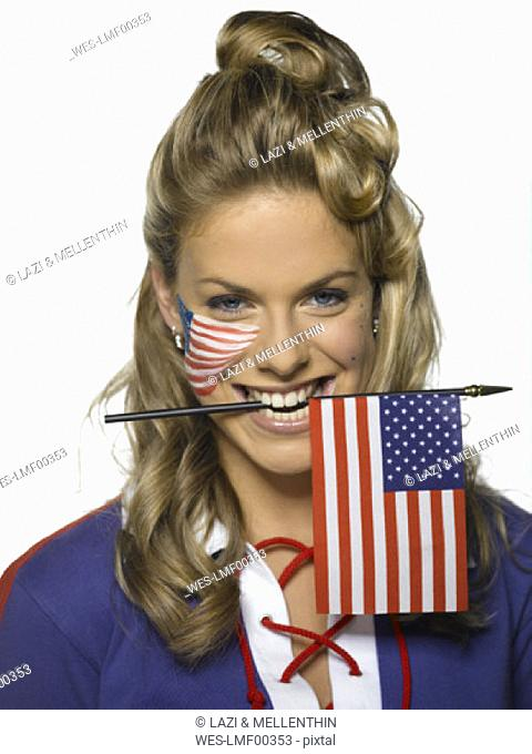 Young woman holding US flag between teeth, portrait
