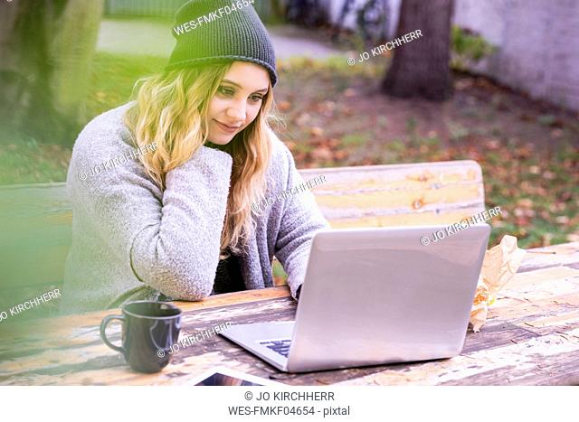 Portrait of smiling young woman with laptop skyping outdoors in autumn