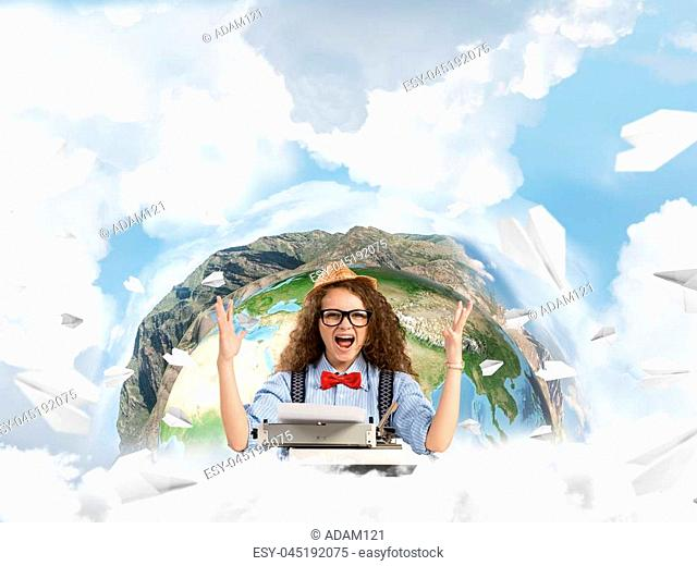Happy and young woman writer in hat and eyeglasses looking happy while sitting with typing machine at the table with flying paper planes and Earth globe among...