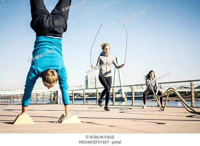 Friends training at the riverside, skipping rope and doing handstand