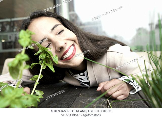 happy woman at fresh basil and chives plants