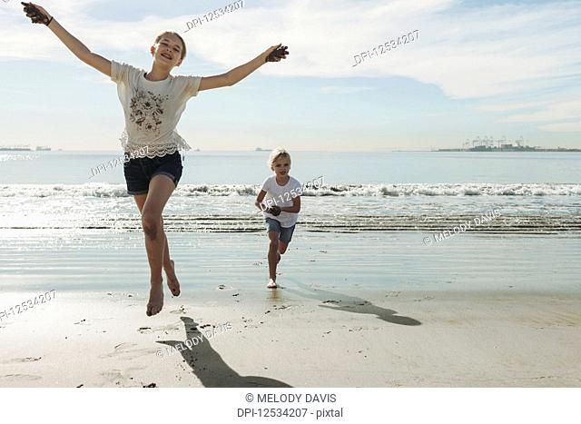 Two sisters running and playing on a beach, the oldest one in front making eye contact with the camera and she leaps into the air; Long Beach, California