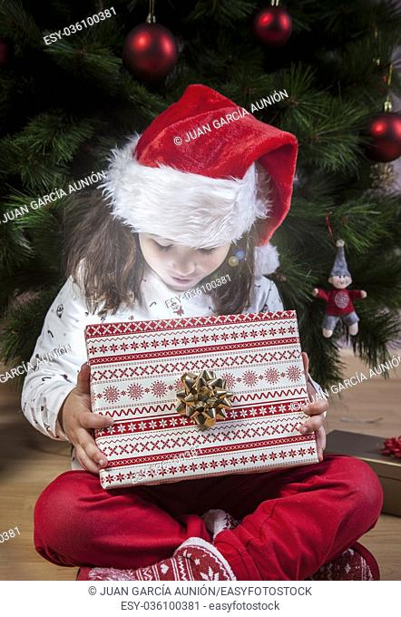 Little girl opening her present beside Christmas tree. She is illuminated by shine from box