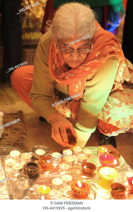CANADA, MISSISSAUGA, 02.11.2013, An elderly Hindu woman lights small earthen lamps (diyas) during the festival of Diwali in a Hindu temple in Mississauga
