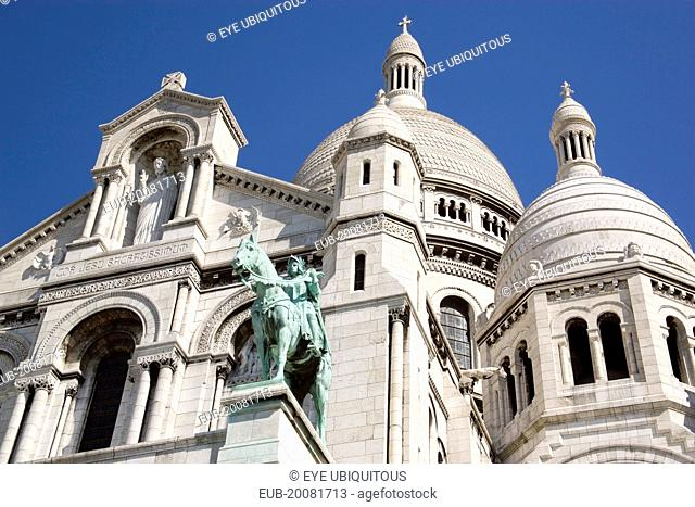 Montmartre The Church of Sacre Coeur or Sacred Heart with the bronze equestrian statue of Joan of Arc in the foreground