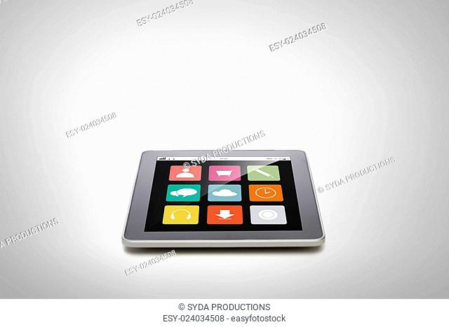 electronics, technology, advertisement and modern gadget concept - black tablet pc computer with menu icons on screen over gray background