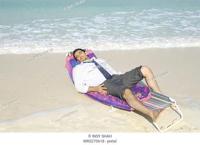 Businessman relaxing in formal wear on the beach