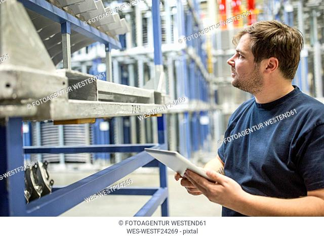 Worker using tablet in factory warehouse