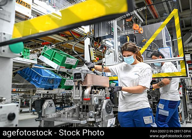 12 May 2020, Baden-Wuerttemberg, Friedrichshafen: In plant two of the automotive supplier ZF Friedrichshafen, mechanic Vanessa is working on a transmission...