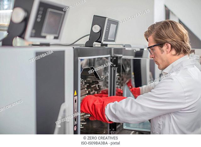 Male worker in thread factory, using chemical oven