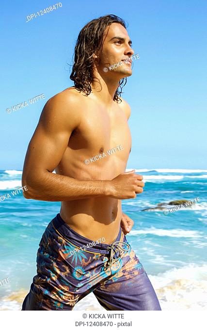 A muscular and shirtless young man runs on the beach at the water's edge wearing a bathing suit; Hawaii, United States of America