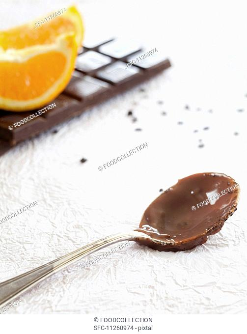 A spoonful of chocolate-orange pudding with ingredients in the background