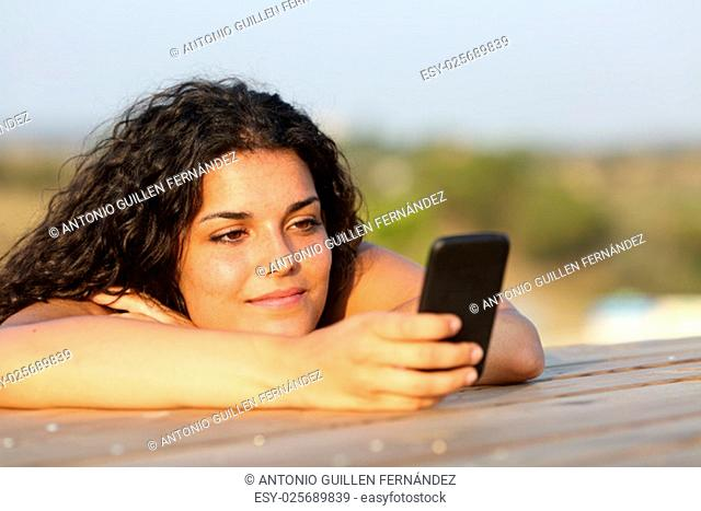 Relaxed girl watching social media in a smart phone in a park or home table with the sky in the background
