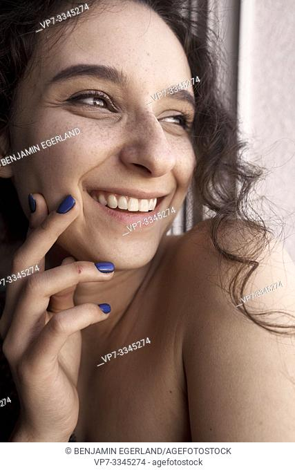 young happy woman peering aside, smiling