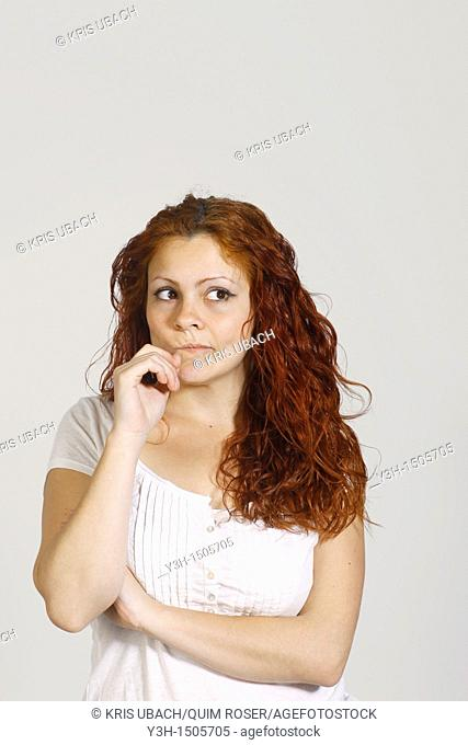 Studio shot of woman, thoughtful