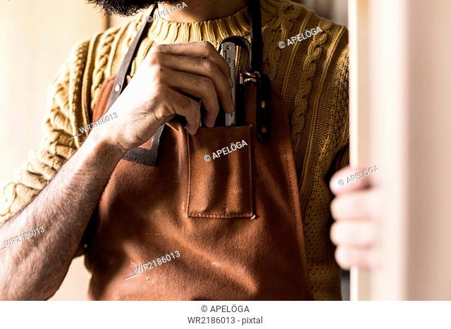 Midsection of carpenter keeping ruler in apron pocket at workshop