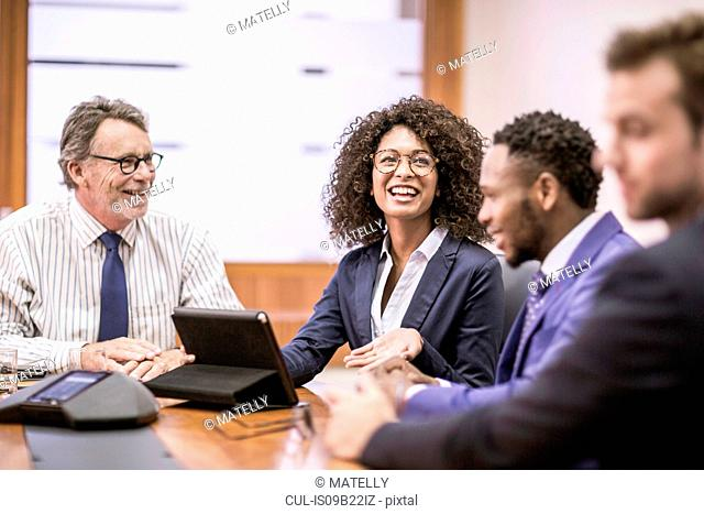Young businesswoman and three businessmen having discussion at boardroom table