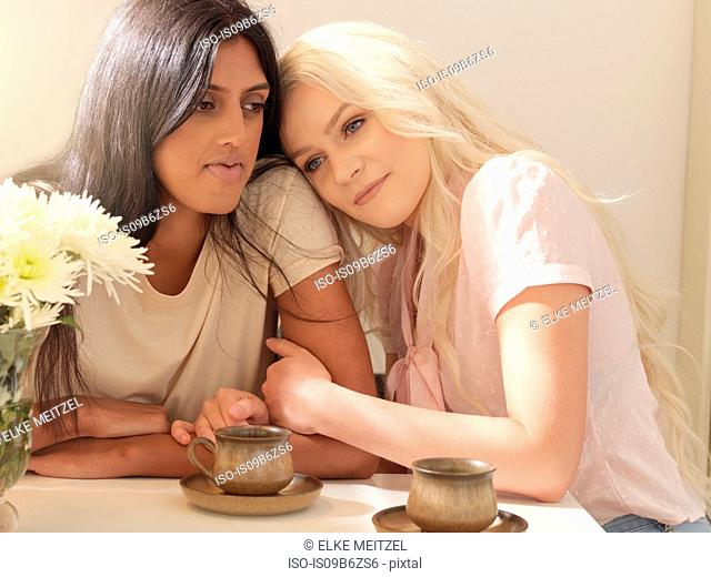 Young woman sitting at table holding friend's arm, coffee cups on table