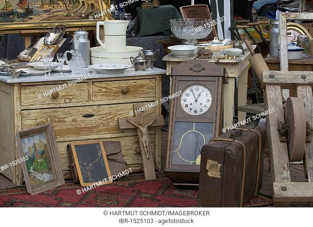 Flea market display, pictures, crucifix, chest of drawers, pendulum clock, suitcase and crockery
