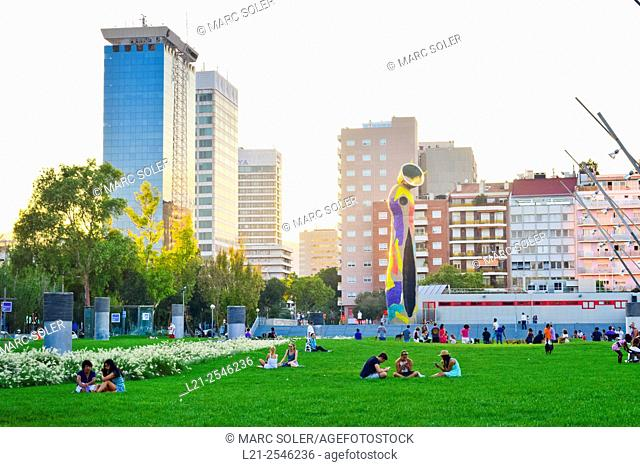 People resting on grass. Office buildings, apartment buildings. Dona i Ocell, Woman and Bird, sculpture by Joan Miró. Joan Miró Park, Barcelona, Catalonia