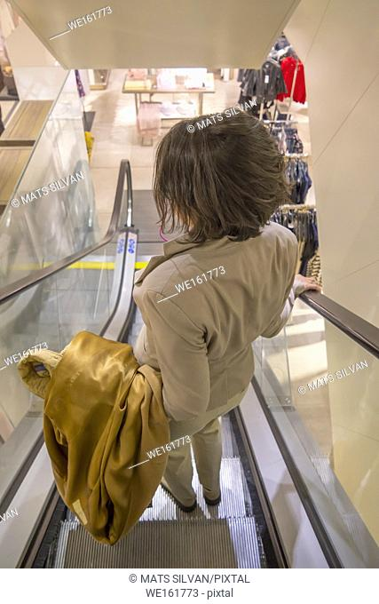 Woman with her Overcoat Hanging on the Arm in a Escalator